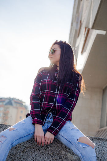Young Woman Sitting On Retaining Wall Against Clear Sky