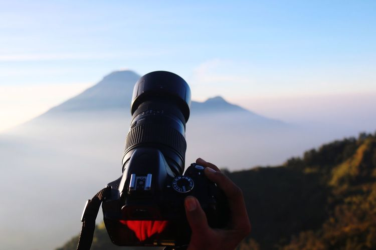 Cropped hand of man photographing against mountains