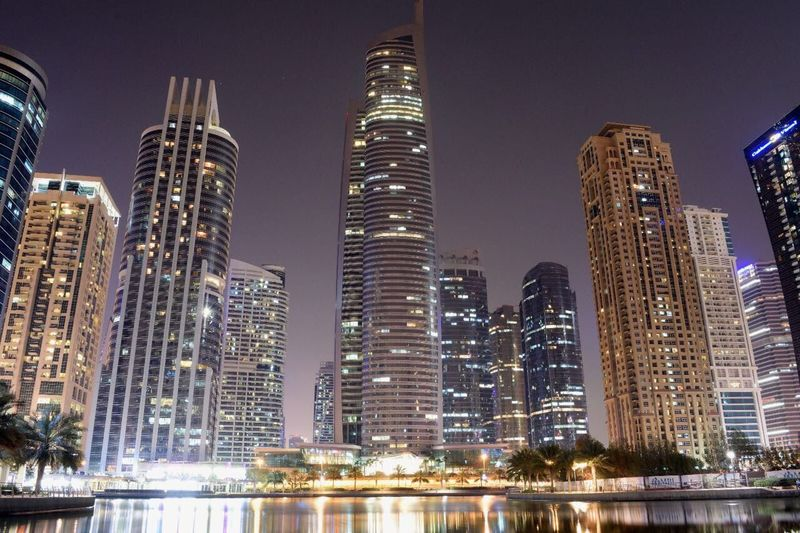 City Building Exterior Architecture Skyscraper Illuminated No People Waterfront Outdoors Modern Low Angle View Built Structure Urban Skyline Sky Water Cityscape JLT Dubai UAE