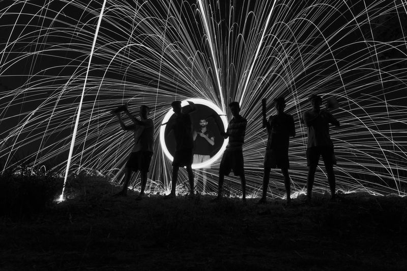 Full length of friends standing against wire wool