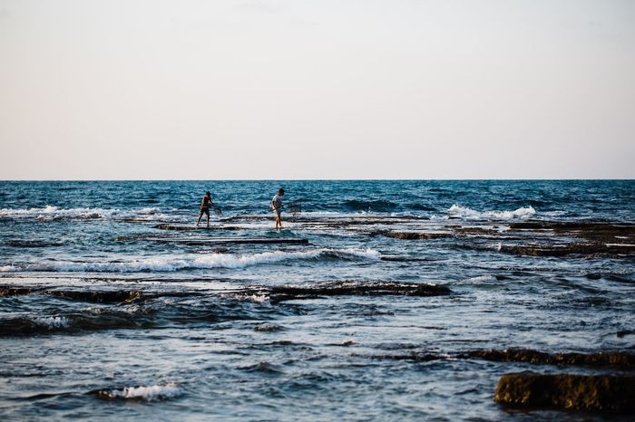 Connected By Travel Local sea shore is a must Sea Horizon Over Water Water Nature Real People Two People Scenics Sky Sport Wave Men Surfing Silhouette Adventure Skill  Paddleboarding Beauty In Nature Outdoors Clear Sky Day Perspectives On Nature