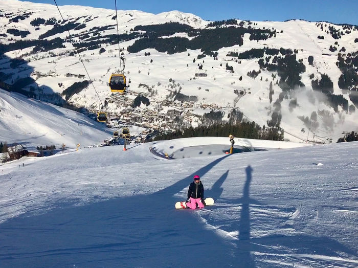 Woman kneeling on snowcapped mountain while snowboarding