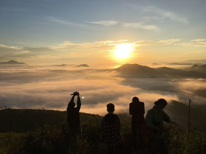 Silhouette people standing on mountain against cloudy sky during sunset