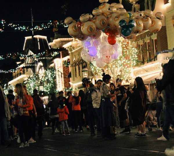 Crowd at illuminated christmas tree in city at night