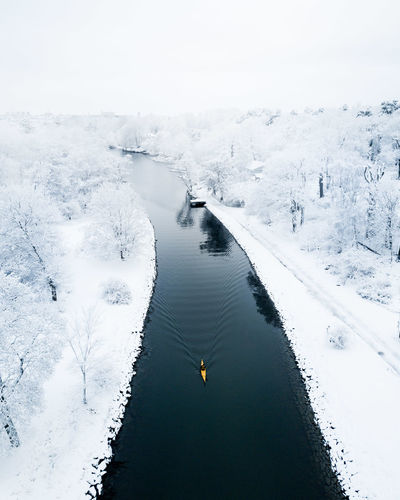 High Angle View Of River Amidst Snow Covered Field