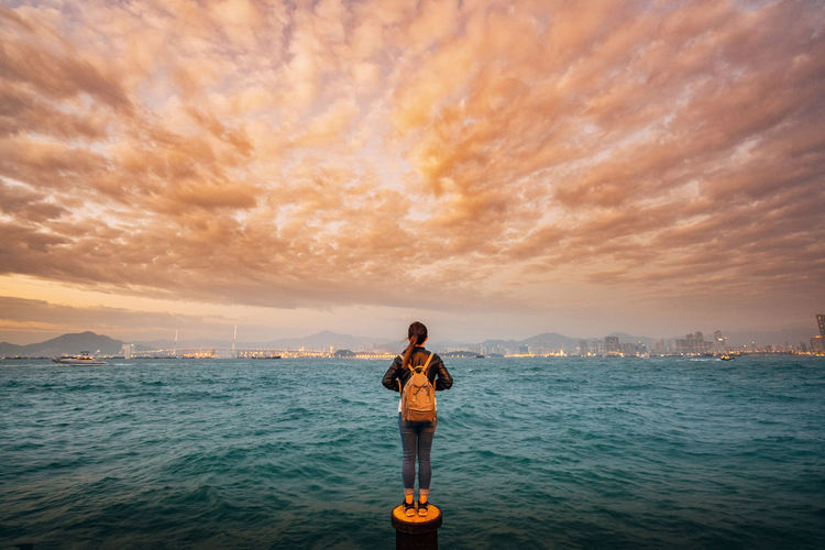 Woman standing over sea against cloudy sky during sunset