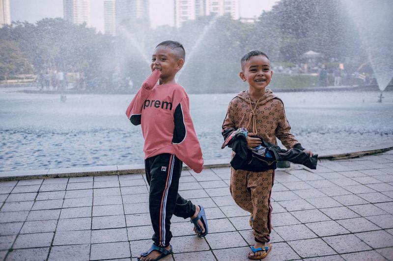 Full length of smiling boy in city