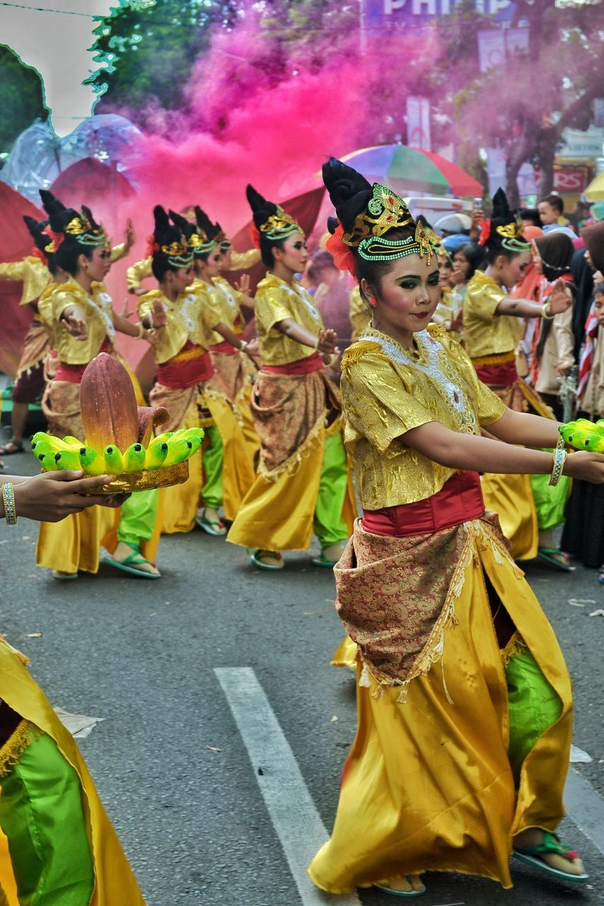 celebration, cultures, large group of people, yellow, dancing, traditional festival, traditional clothing, tradition, men, real people, togetherness, enjoyment, day, lifestyles, outdoors, happiness, traditional dancing, women, performance, full length, adult, people