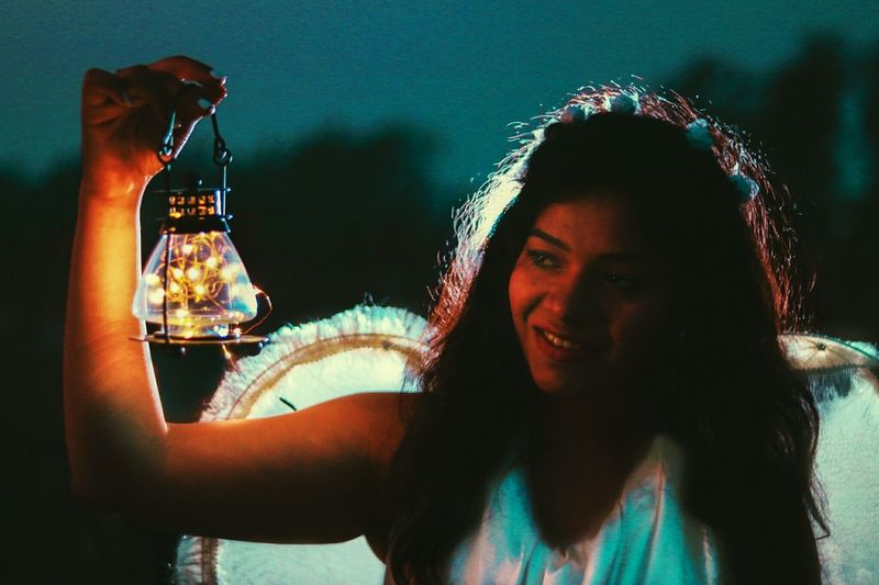 Close-Up Of Smiling Young Woman Holding Illuminated String Light While Standing Outdoors At Dusk