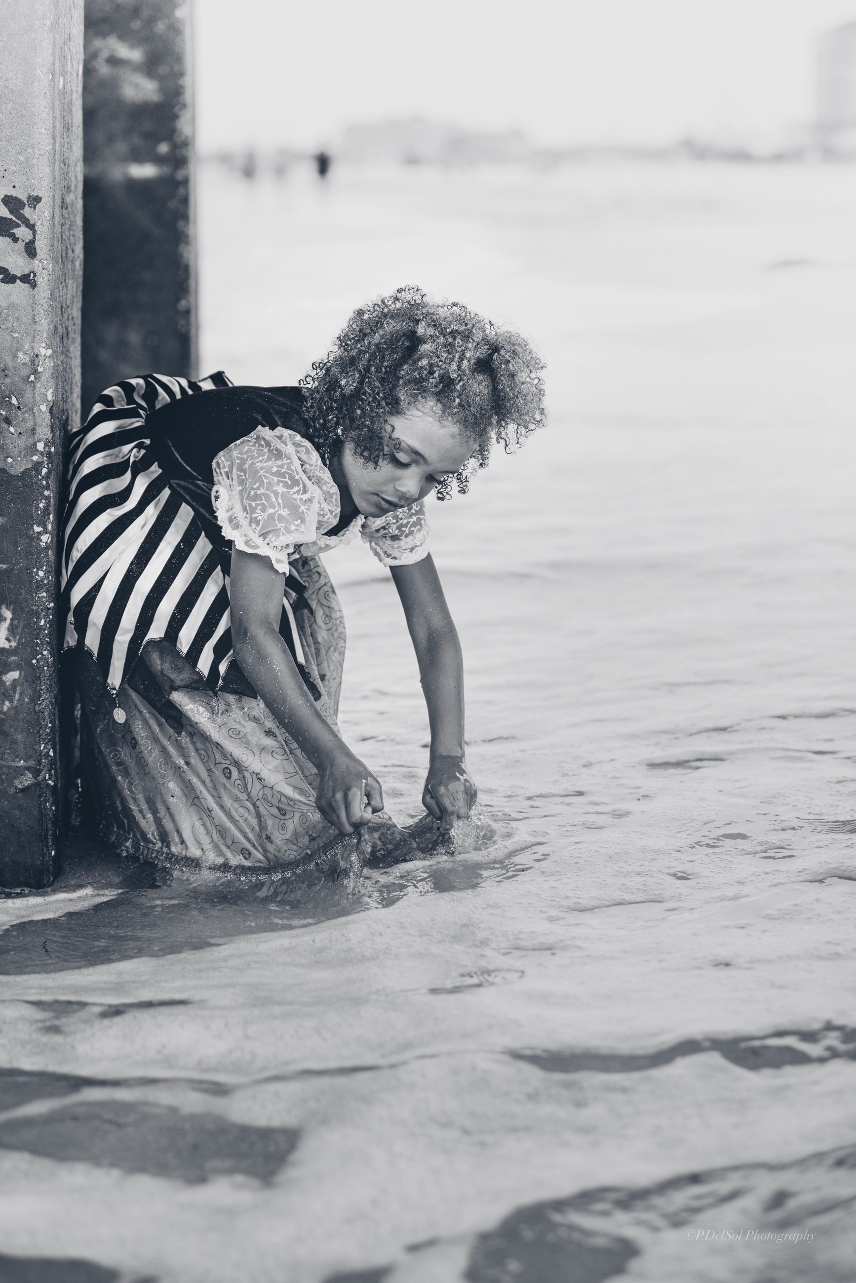 one person, water, real people, leisure activity, land, lifestyles, child, nature, side view, beach, day, childhood, females, sea, women, curly hair, outdoors, hairstyle
