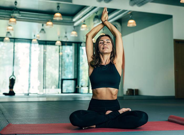 Full length of woman doing yoga on floor