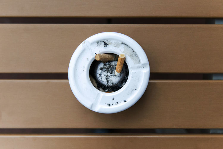 Close-Up Of Cigarette In Ashtray At Table