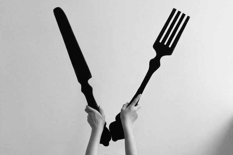 Cropped Hands Holding Large Fork And Table Knife Against Gray Background