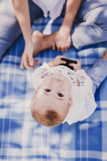 Directly above portrait of baby girl sitting by mother on picnic blanket
