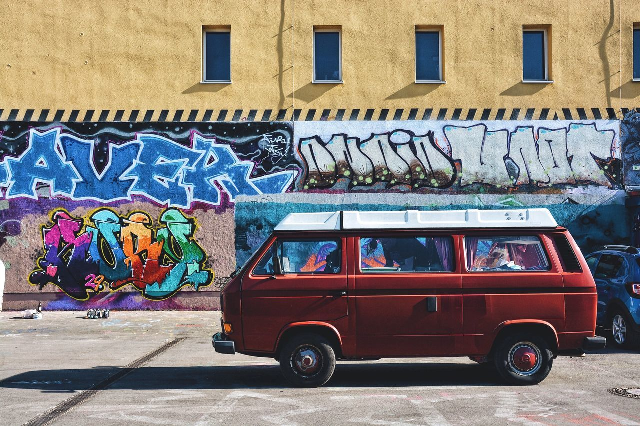 Van on street against graffiti on building during sunny day