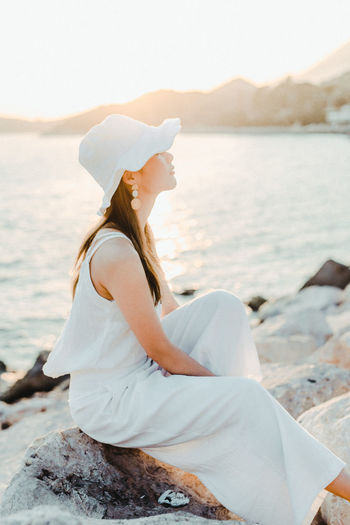 Water One Person Leisure Activity Lifestyles Real People Sea Sitting Beauty In Nature Women Side View Nature Rock Relaxation Adult Casual Clothing Young Women Rock - Object Young Adult Hairstyle Outdoors Looking At View