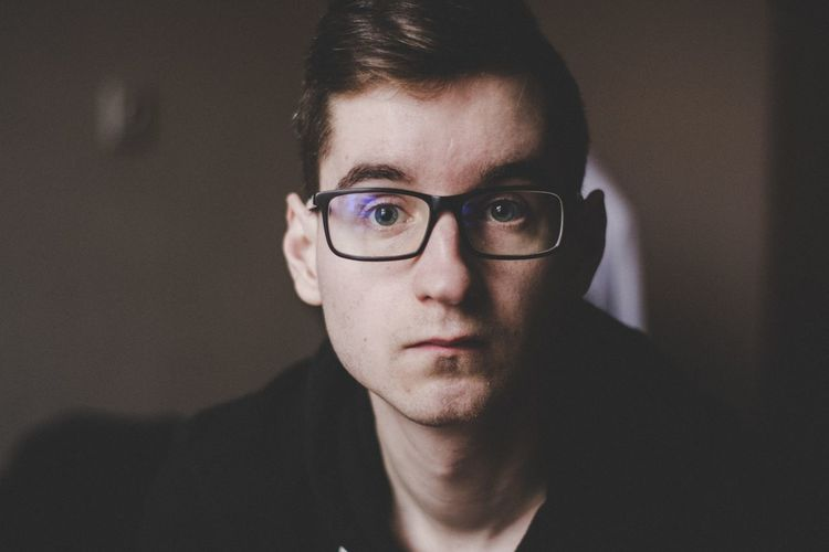 Portrait Of Young Man Wearing Eyeglasses At Home