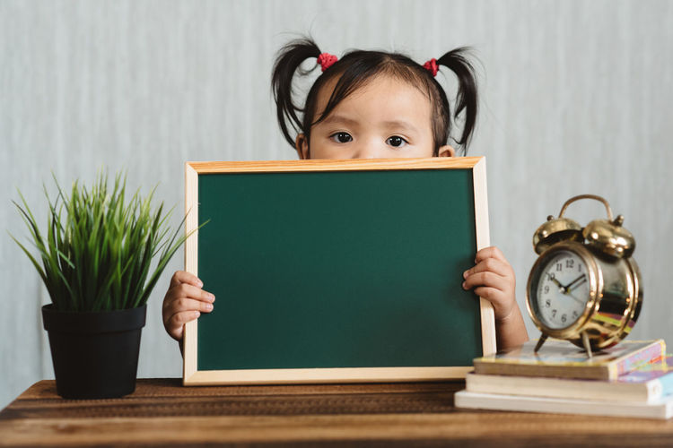Portrait of girl holding slate on table at home