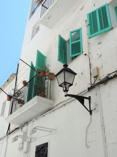 Beautiful building facade of an old Vila. Ibiza Apartment Architecture Balcony Building Building Exterior Built Structure City Dalt Vila Day Electric Lamp House Lighting Equipment Low Angle View Nature No People Old House Outdoors Railing Residential District Street Light Turquoise Colored Wall - Building Feature White Color Window