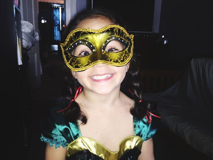 Portrait of happy girl wearing masquerade mask at home