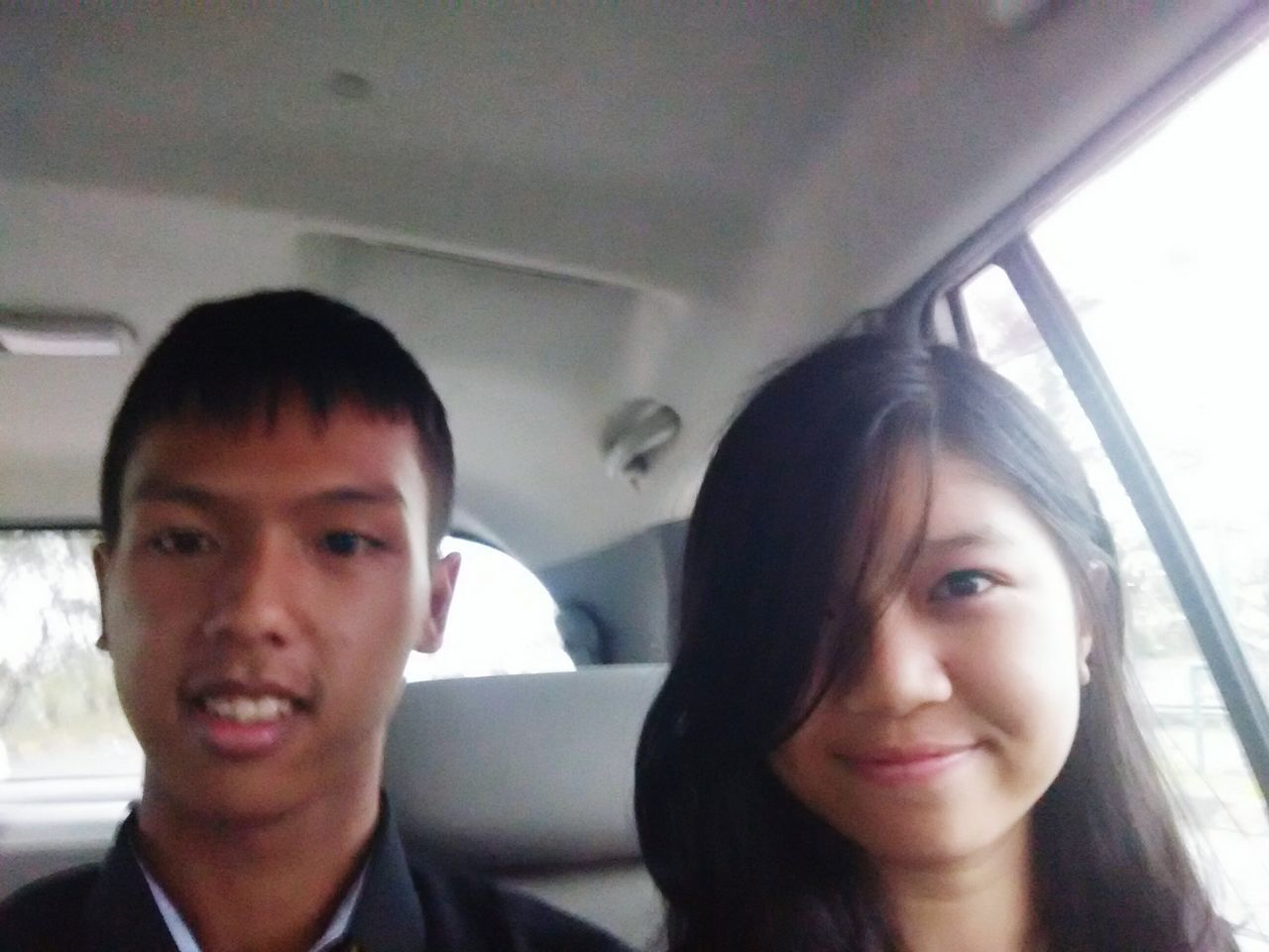 two people, vehicle interior, transportation, car interior, car, looking at camera, real people, young adult, young women, portrait, land vehicle, front view, mode of transport, togetherness, smiling, headshot, lifestyles, young men, day, happiness, close-up, outdoors