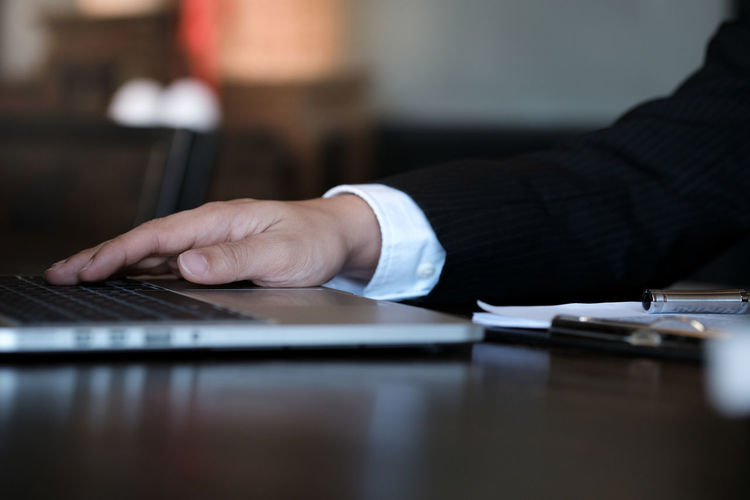 Cropped hand of judge holding hand on laptop on table at office