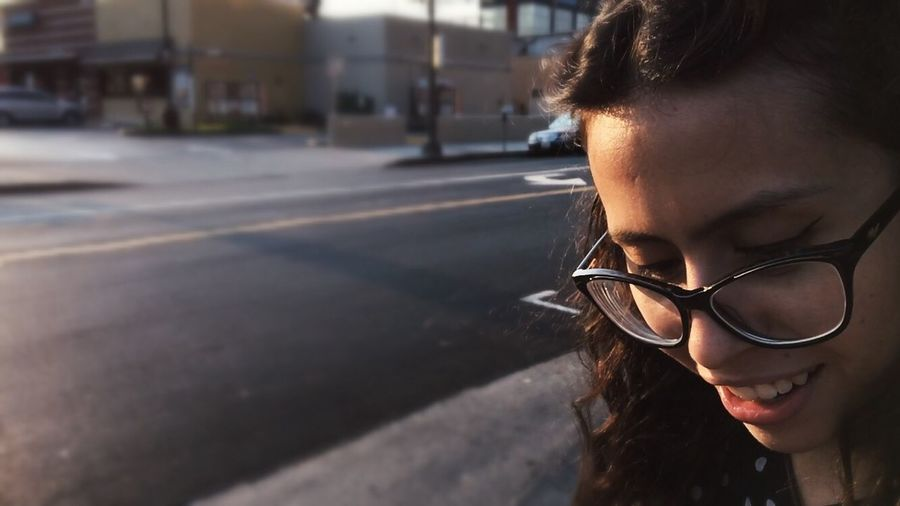 Close-up of smiling woman with eyeglasses on road