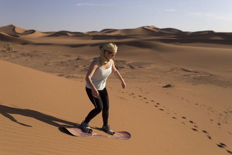 Full length of teenage girl sandboarding in desert