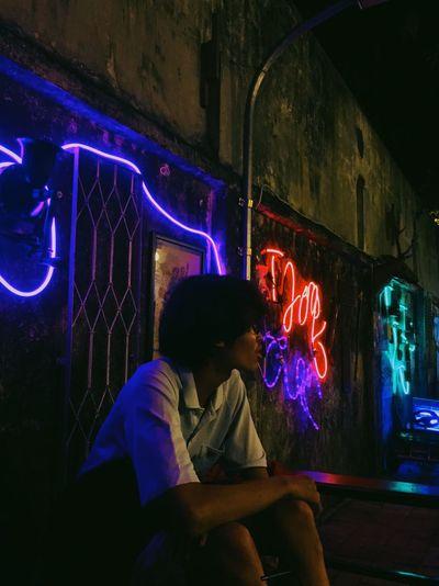 Man looking at illuminated while sitting on wall at night