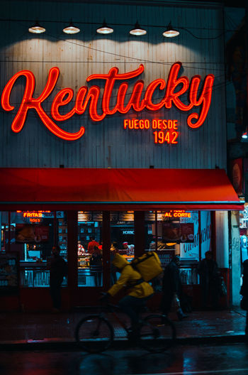 Kentucky Sign Architecture Building Exterior Built Structure City City Life Commercial Sign Communication Illuminated Lifestyles Men Neon Neon Lights Night Outdoors People Real People Sign Store Store Sign Street Streetphotography Text Transportation Western Script