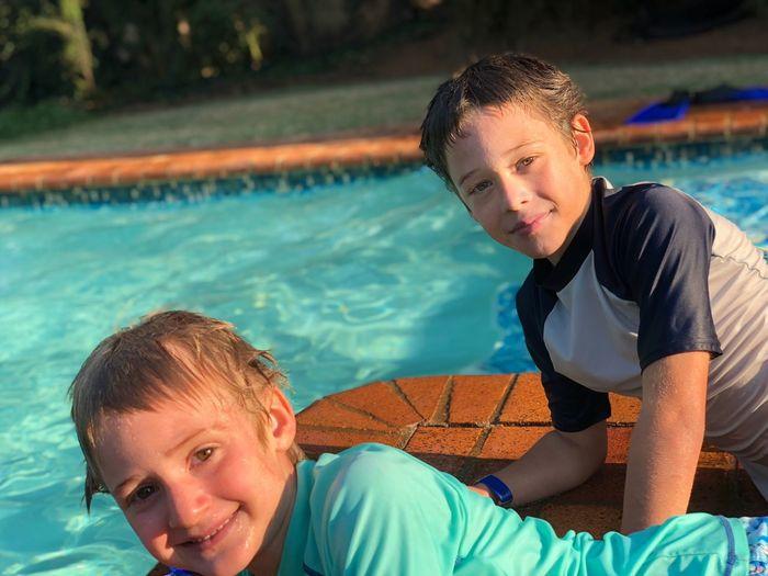 Portrait of siblings lying at poolside