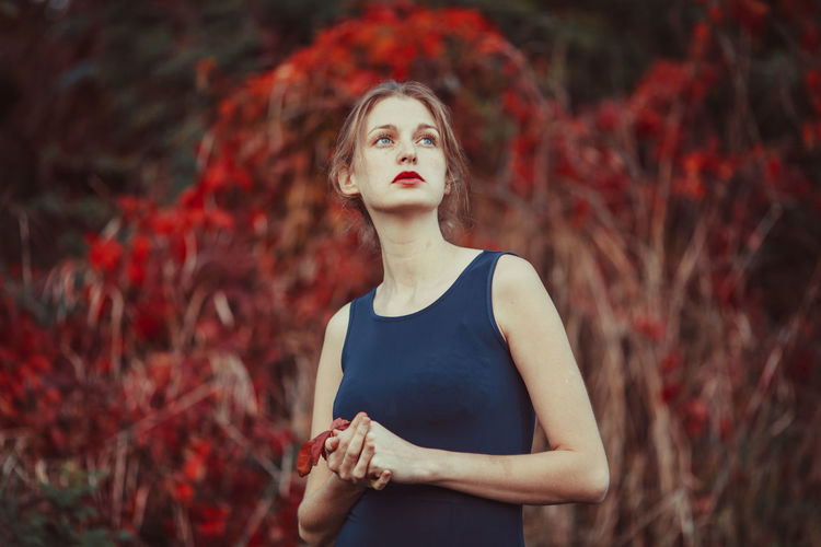 Young woman looking away while standing in autumn
