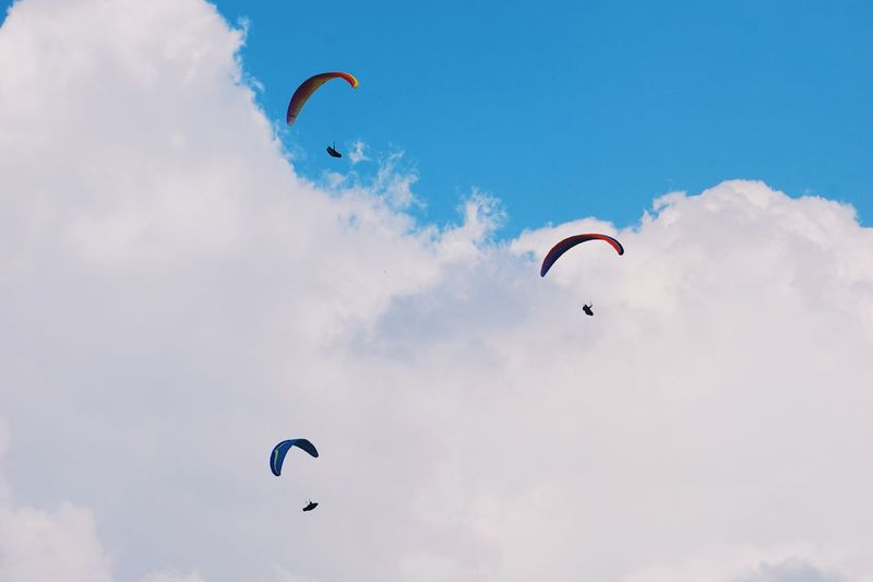 Low angle view of people paragliding against cloudy sky