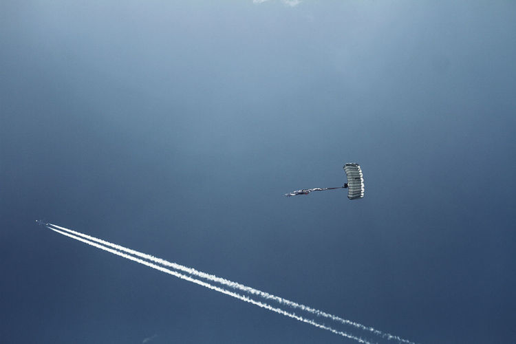 Low angle view of vapor trail and parachute flying against clear sky