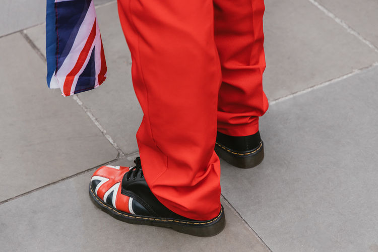 Low section of man holding british flag while standing in city
