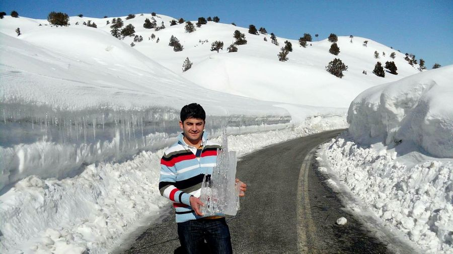 Portrait of man holding ice while standing on road against snowcapped mountain