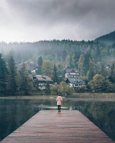 Beauty In Nature Day Full Length Lake Leisure Activity Lifestyles Looking At View Mountain Nature One Person Outdoors Pier Real People Rear View Scenics - Nature Sky Tranquil Scene Tranquility Tree Water