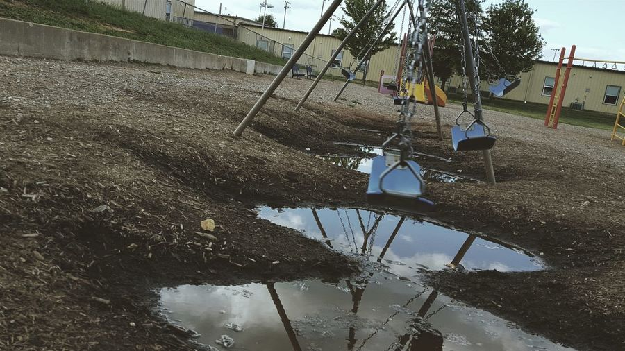 Low Angle View Swingset From Childhood Playground Play Swing Fun Water Puddles