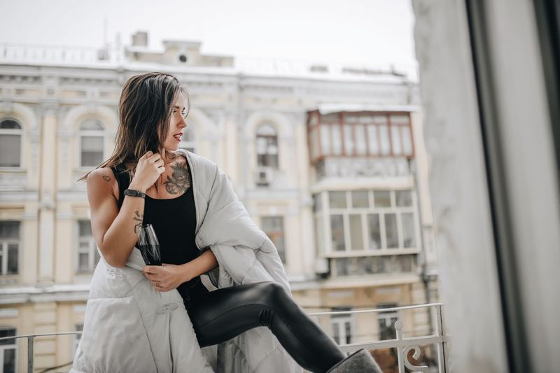 Woman with wineglass wearing blanket while standing at balcony during winter