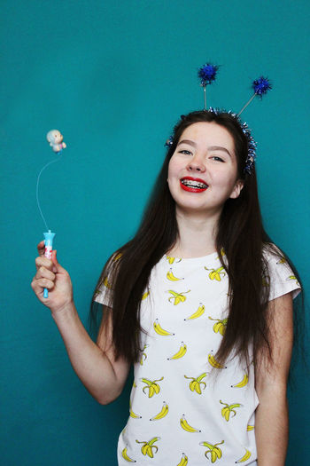 Portrait Of Happy Woman Holding Toy Against Blue Background