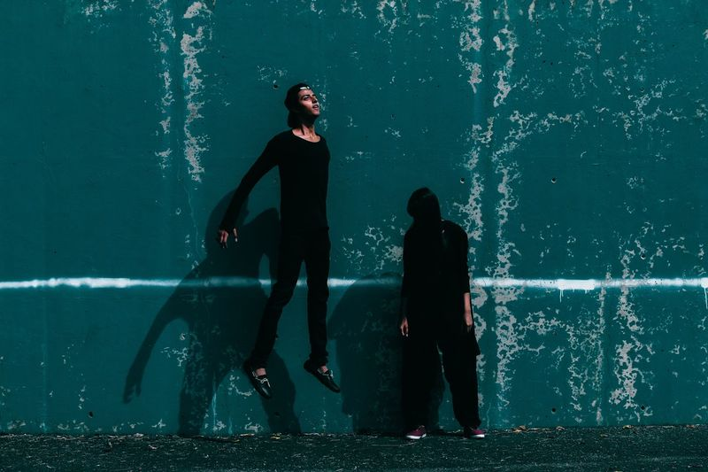 Man in mid-air while woman standing against wall