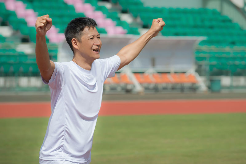Happy sportsman with arms raised walking on field