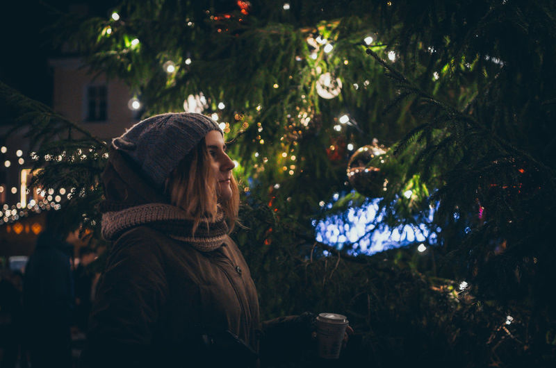 Woman On Illuminated Christmas Tree At Night