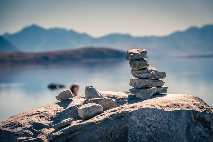 Stack of rocks by lake against sky