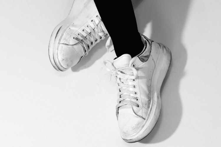 Low Section Of Person Wearing Shoes Over White Background