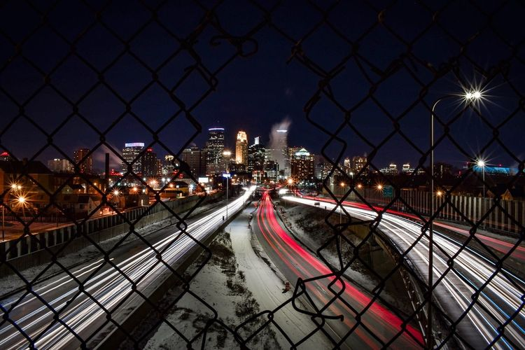 Light trails on railroad tracks in city seen through broken fence