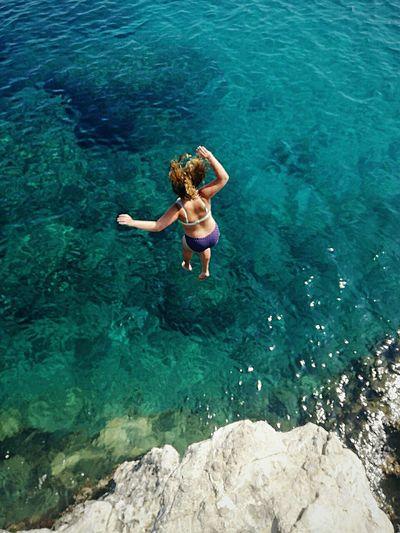 High angle view of woman wearing bikini jumping in sea