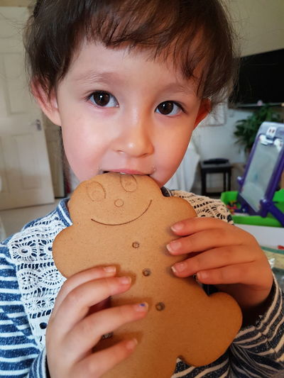 Portrait of cute girl eating gingerbread cookie at home