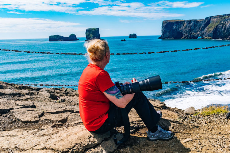 Side view of woman with camera sitting on rock formation by sea during sunny day