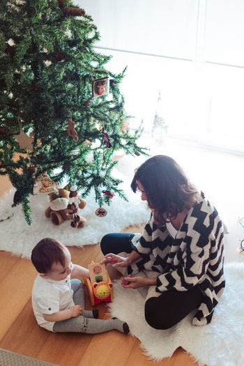 Rear view of girl sitting by christmas tree on floor